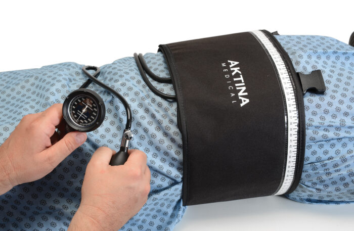 Respiratory Compression Belt on Patient Lying Down with Person Using the Bulb Gauge