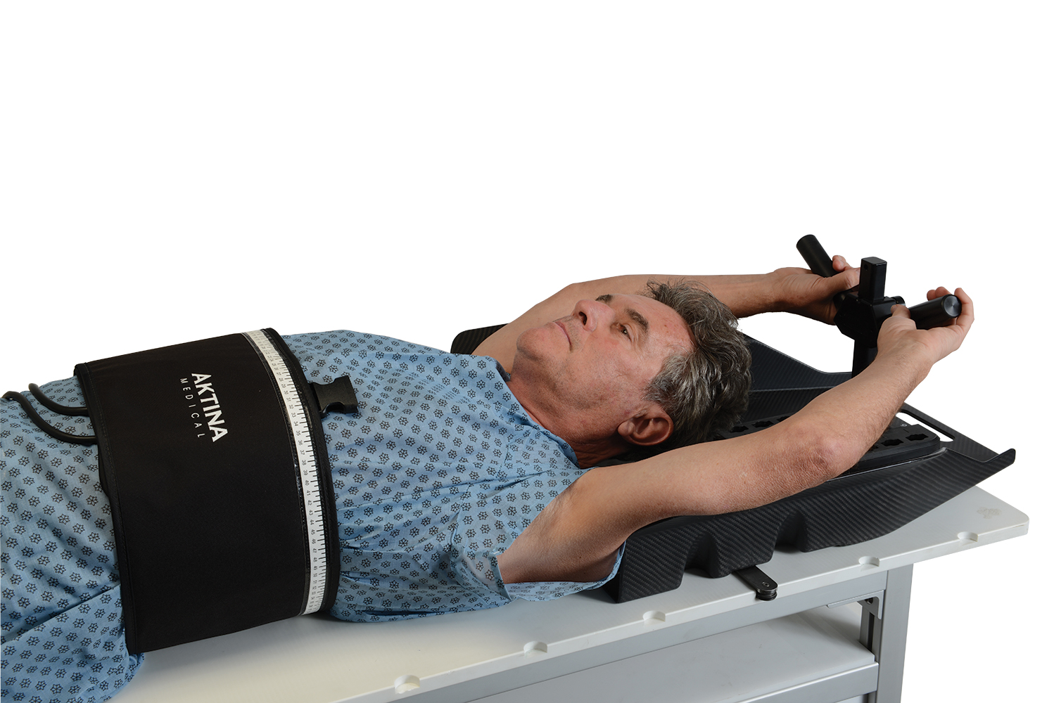 Man lying on SBRT board with ArmCradle 4 Y handle and compression belt